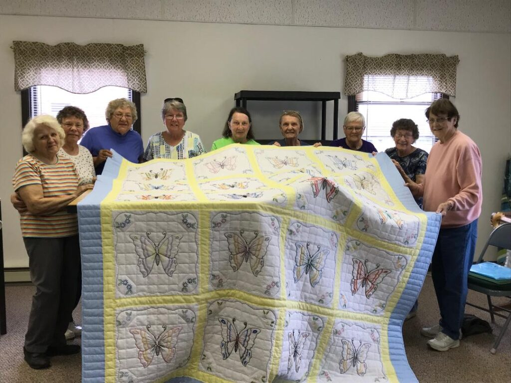 Woman holding the BUtterfly Quilt