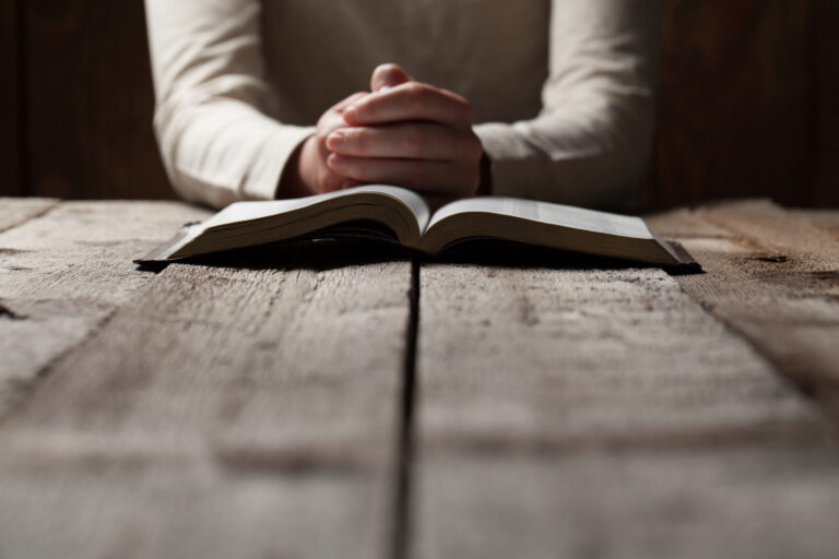 Person Praying with Bible in front of them